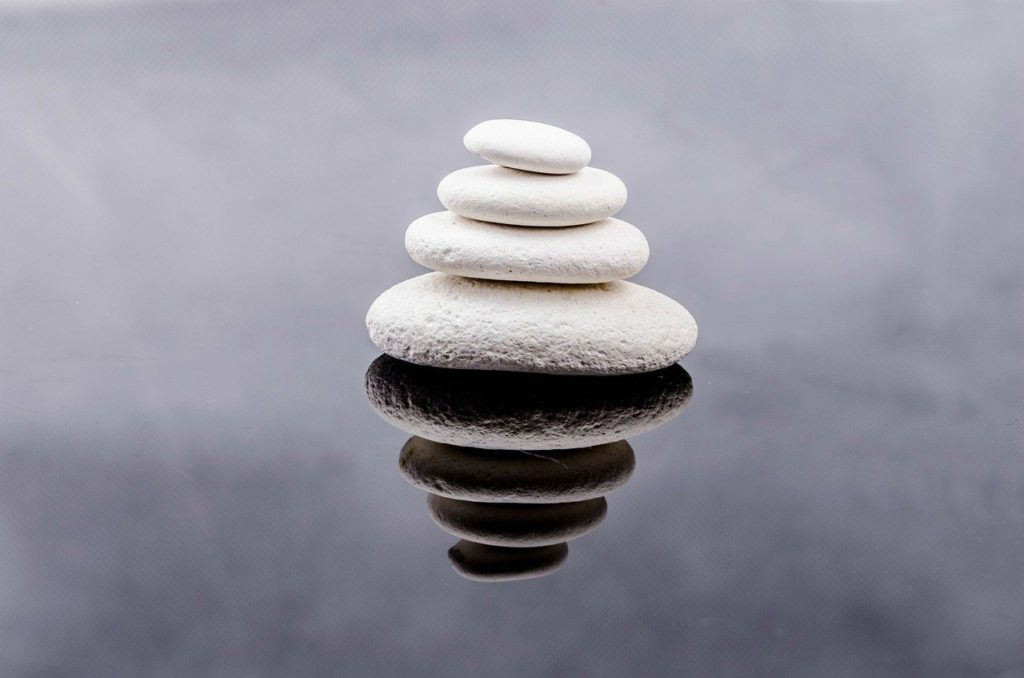 calming balanced white rocks with reflection