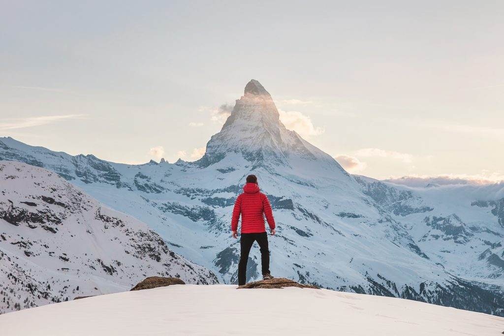 confident person in red jacket facing a large majestic mountain